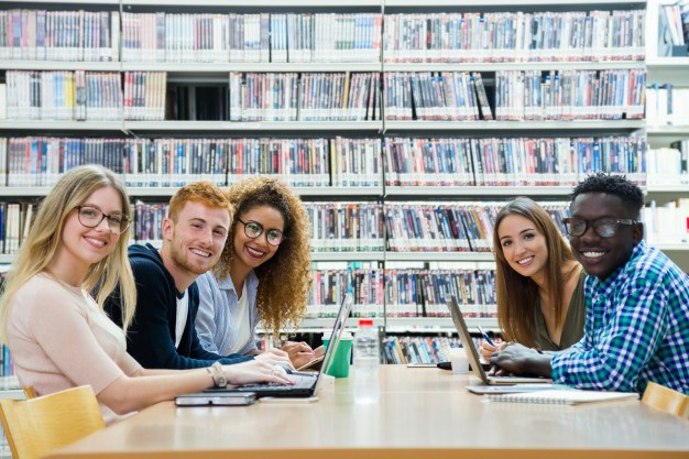 Group of happy exchange students working in the library